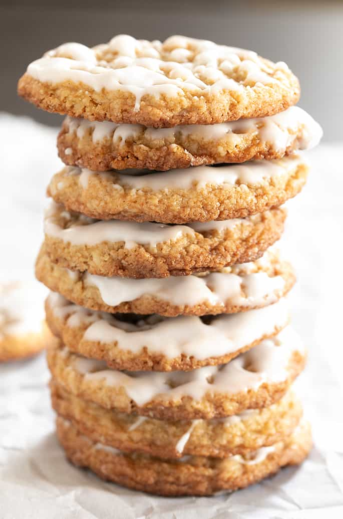 Tall stack of iced thin and chewy gluten free oatmeal cookies.