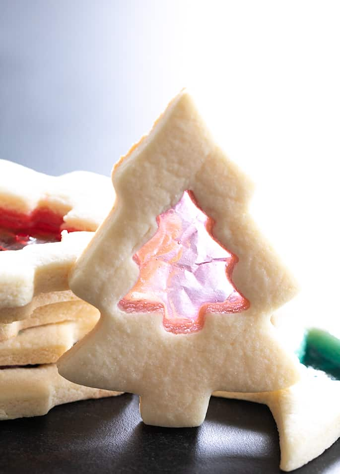 one stained glass sugar cookie shaped like a Christmas tree standing up