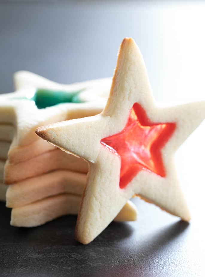 Stack of stained glass gluten free sugar cookies shaped like stars with one standing up