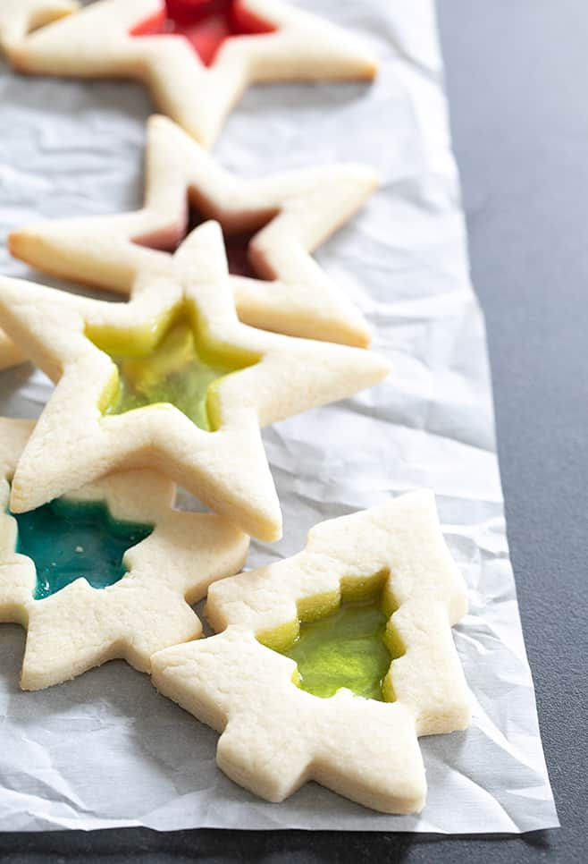 Image of pile of stained glass gluten free sugar cookies shaped like stars and Christmas trees