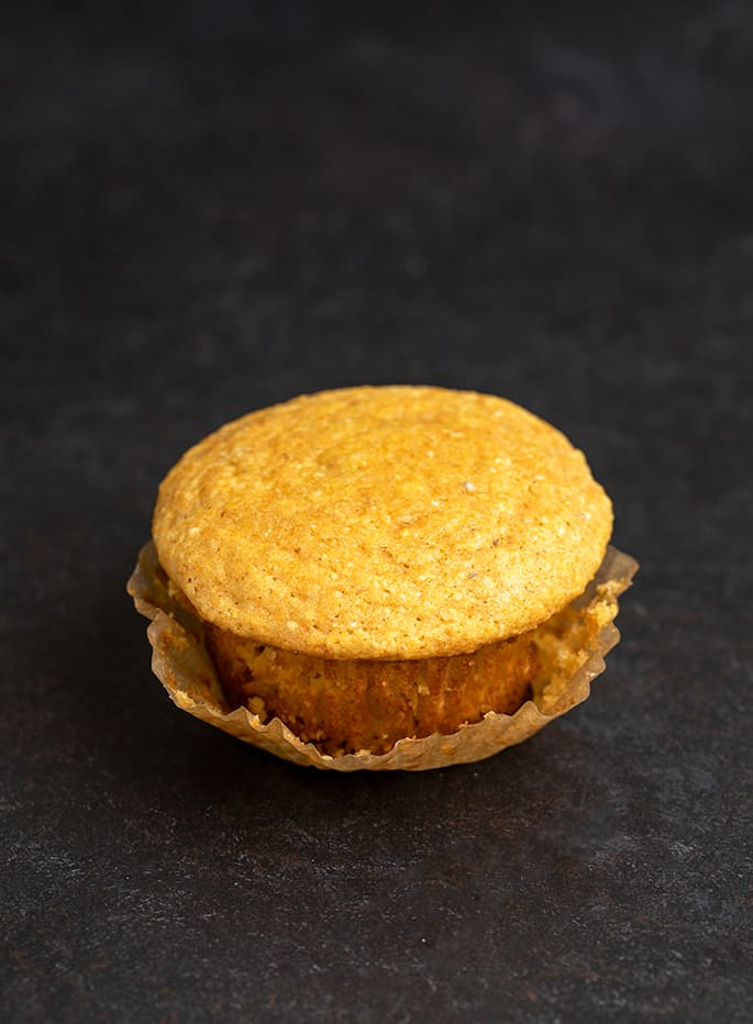 Image of single corn muffin on black surface with brown muffin wrapper pulled down partially