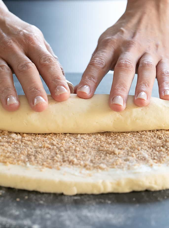 How to shape easy gluten free cinnamon rolls into a log that is ready to be sliced into 6 pieces.