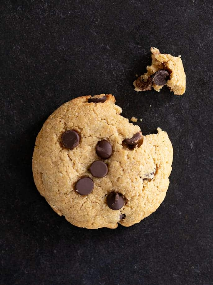 Overhead image of one chocolate chip protein cookie, with a corner broken.