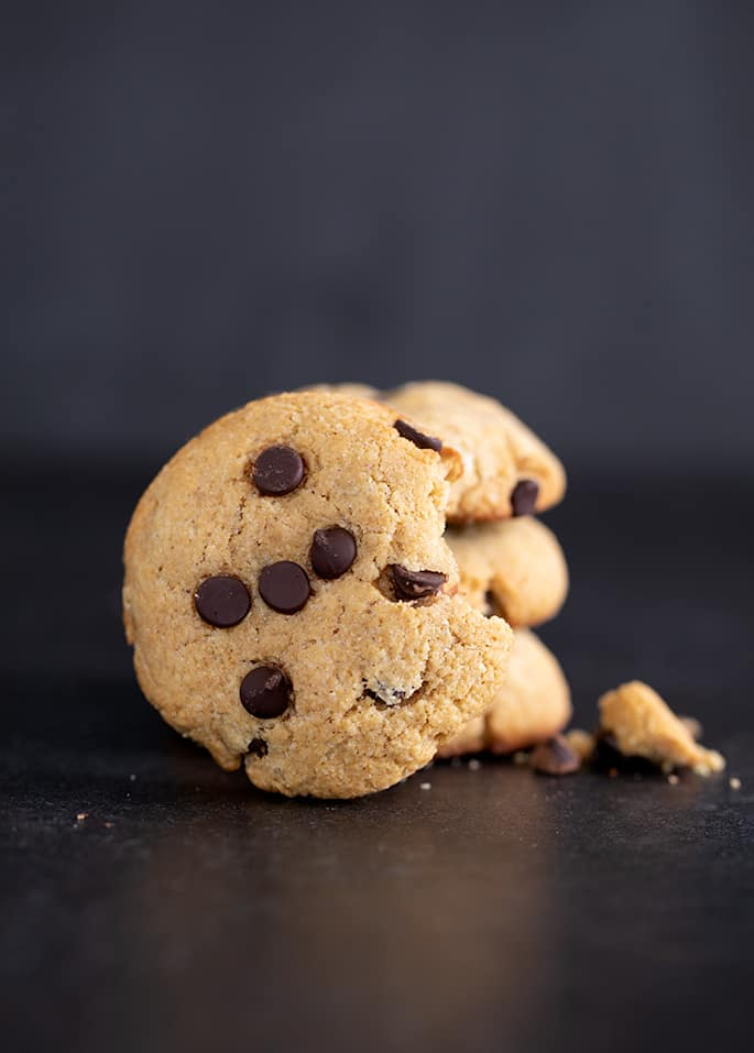 Chocolate chip protein cookies in a small stack with one cookie facing forward, broken.