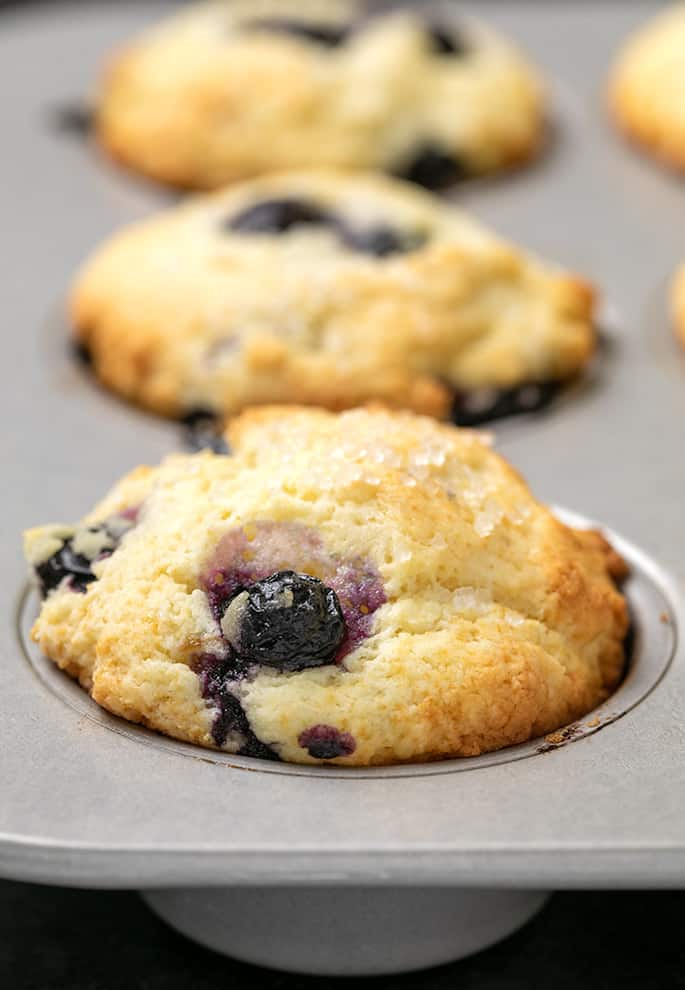 3 baked blueberry muffins in metal muffin tin