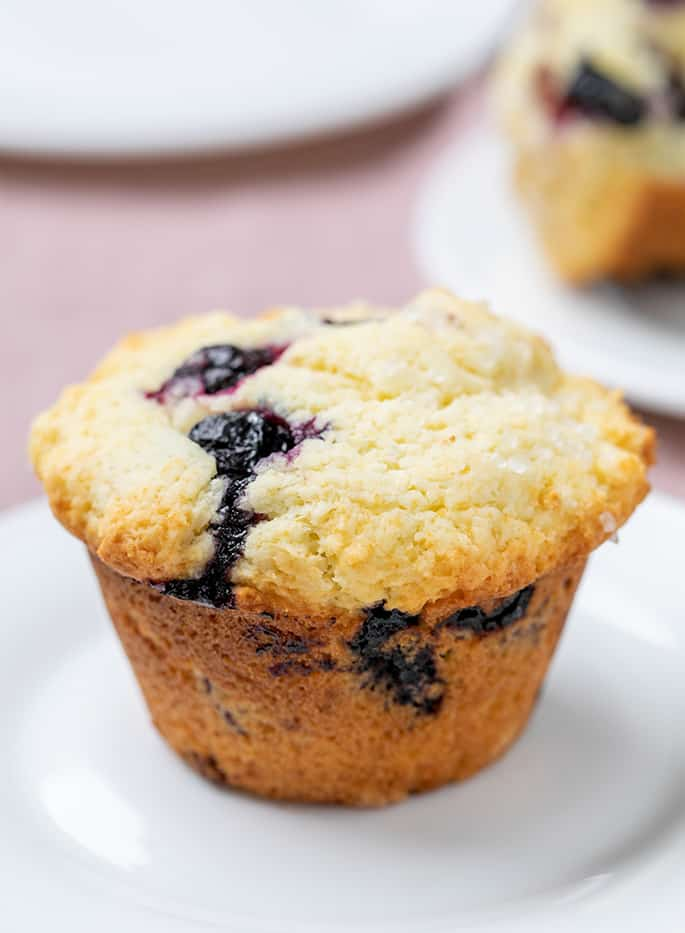 Blueberry muffin on small white round plate with more plates in background on purple cloth