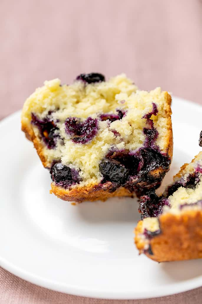 Blueberry muffin split in half on small white plate on light purple cloth
