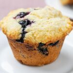 Square image of one blueberry muffin on a small white plate