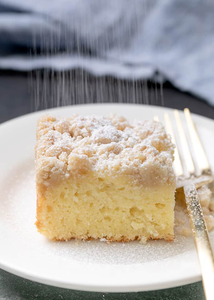 Powdered sugar being sprinkled on square of crumble-topped coffee cake on white plate with fork