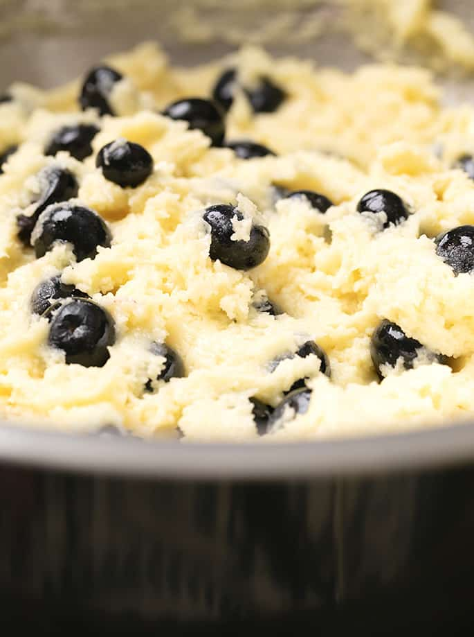 Raw muffin batter with blueberries in metal bowl