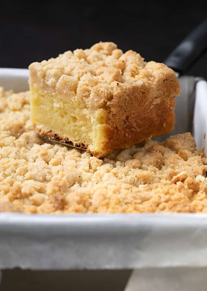 Square slice of coffee cake being lifted out of square pan lined with white paper
