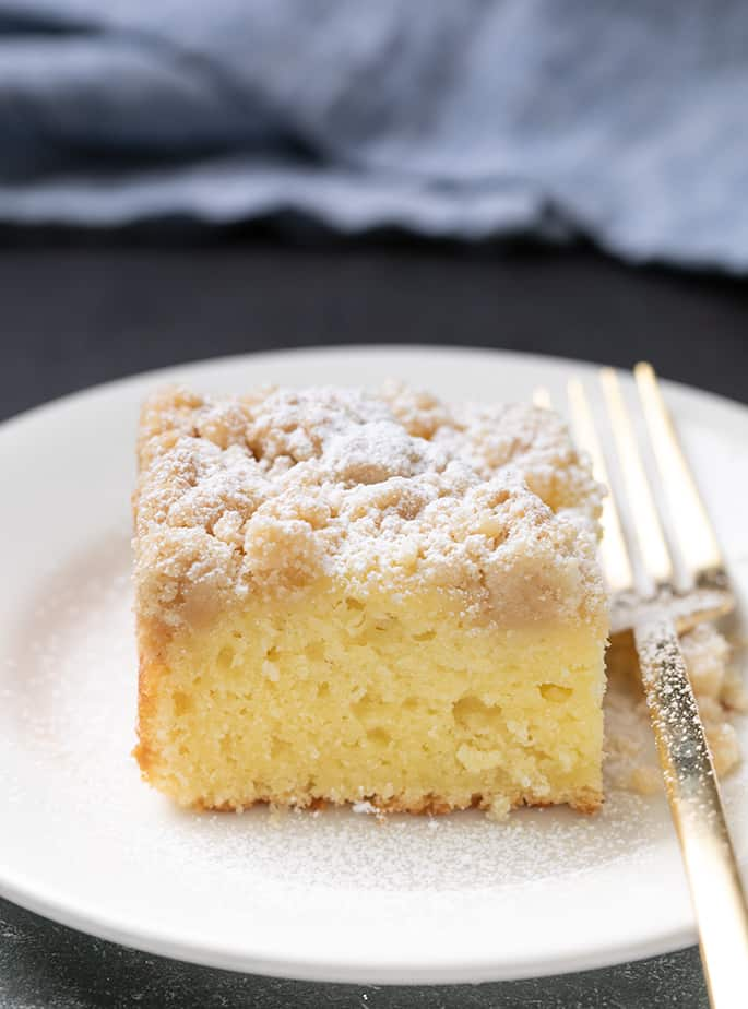 Square slice of crumble topped coffee cake with fork on small round white plate with blue cloth in background