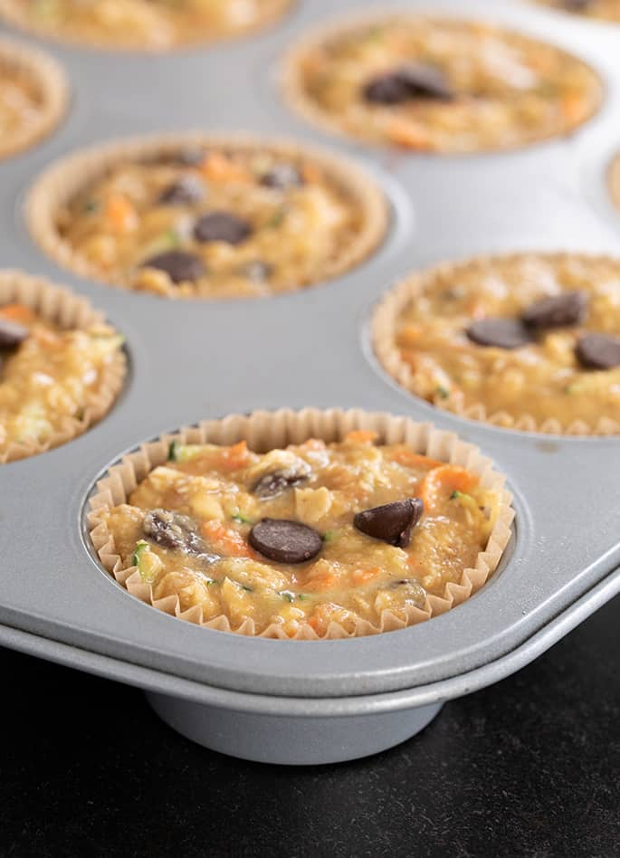Superfood muffins raw in the wells of a muffin tin, ready to be baked.