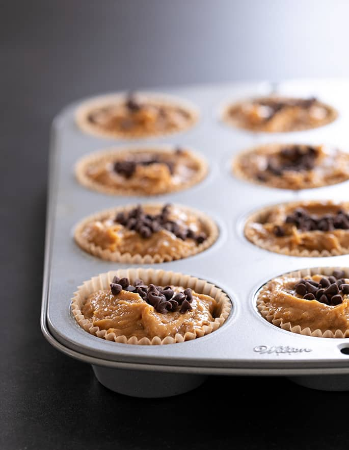 Flourless peanut butter muffins, made with no flour, no banana, and no dairy, pictured raw in the muffin tin, ready for the oven.