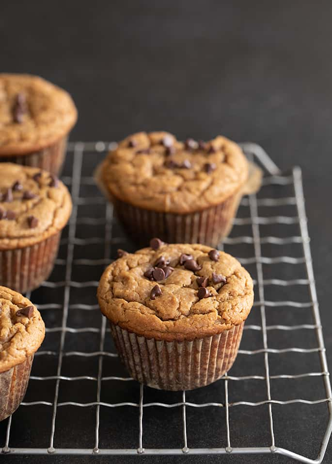 Flourless peanut butter muffins whole muffins on a wire rack.