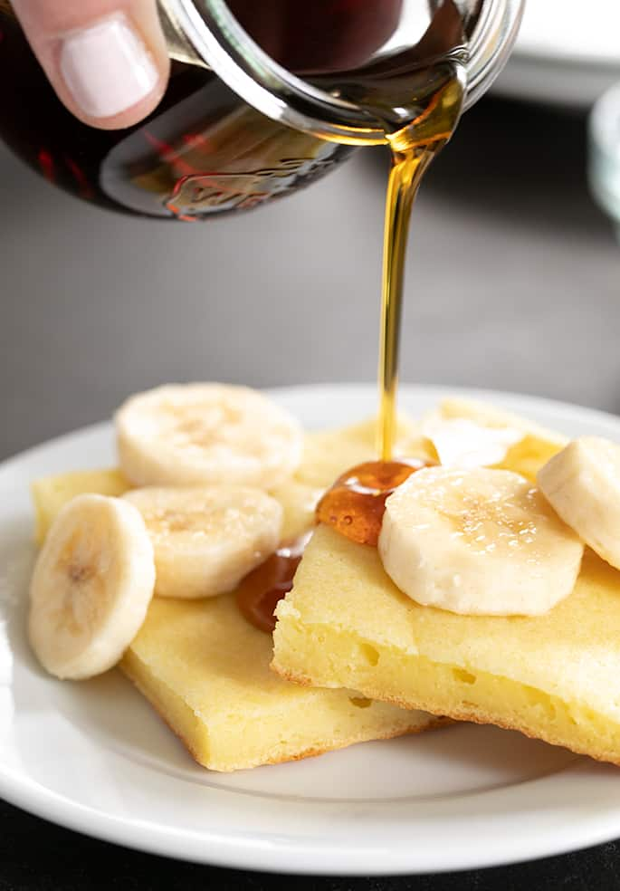 A close up of a plate of sheet pan pancakes with bananas and syrup