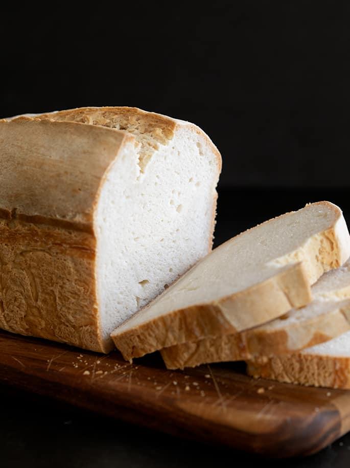 A cut in half gluten free sourdough bread, sitting on top of a wooden cutting board
