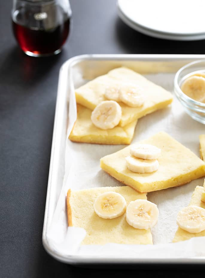 Gluten free pancakes made in a sheet pan, sliced on the baking tray, served with sliced bananas and maple syrup.