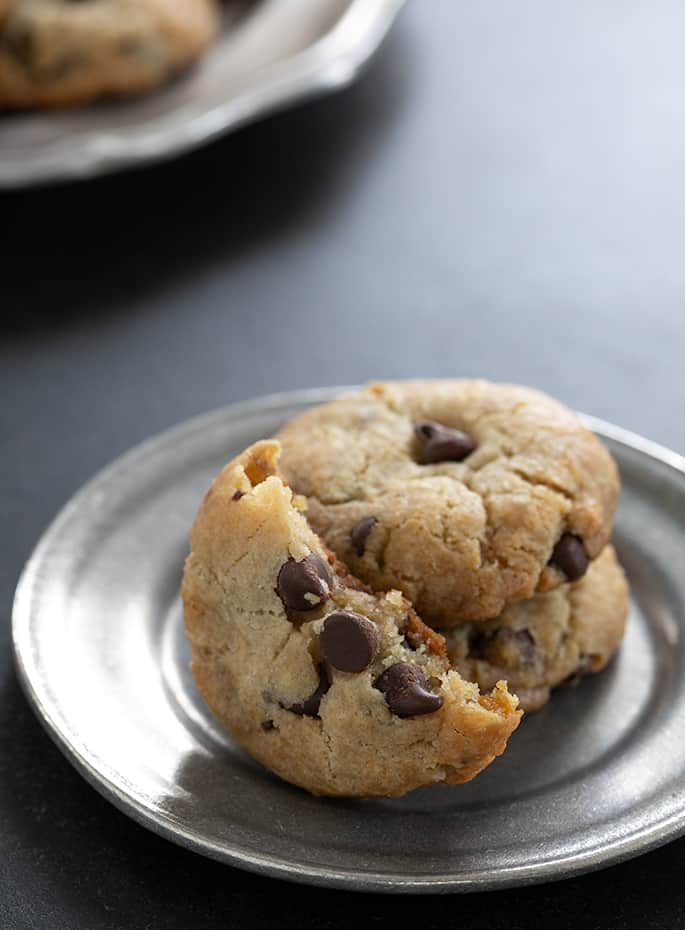 Vegan gluten free chocolate chip cookies with a view of the crisp edges and extra chewy inside.