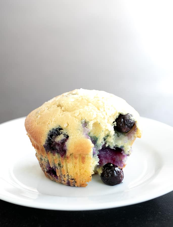 Gluten free blueberry muffin with rice flour pictured with a bite taken and a blueberry falling out.