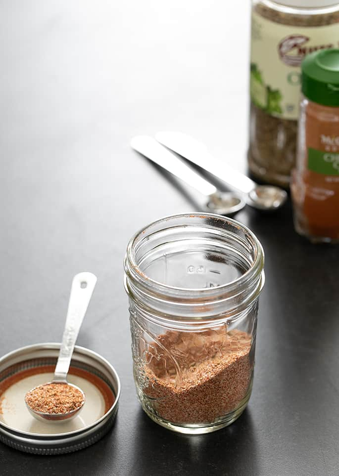 Gluten free taco seasoning in jar, with a teaspoonful beside the jar.