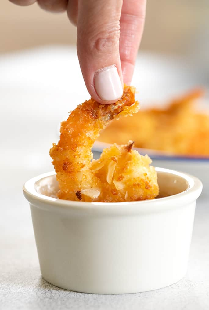 Coconut shrimp being dipped into small ramekin of sauce