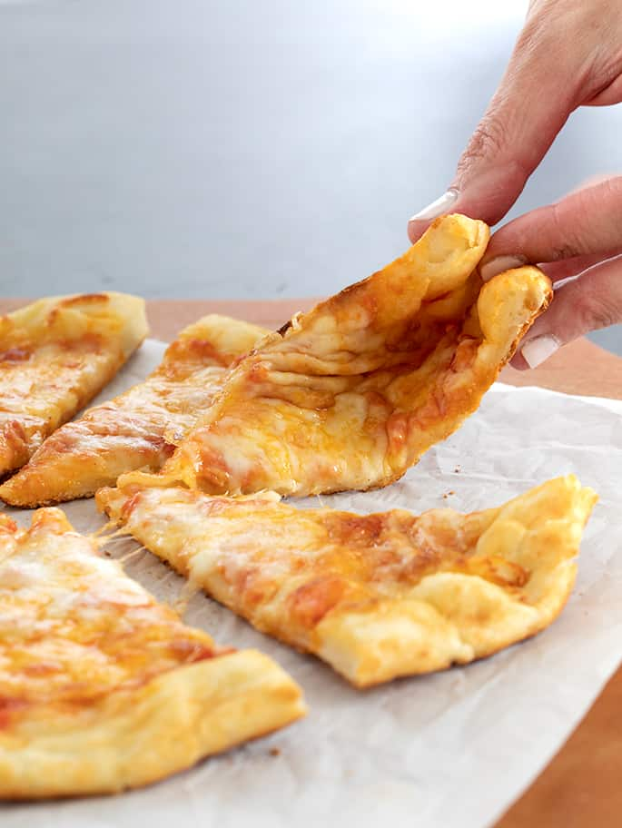Fingers folding a piece of NY style pizza in a pie of slices