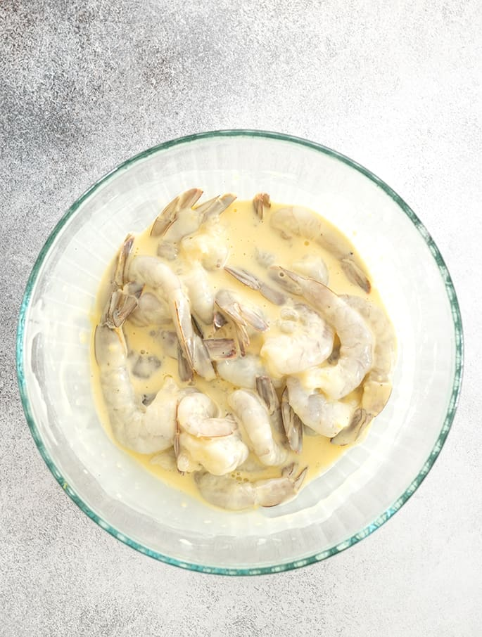 Raw shrimp soaking in batter
