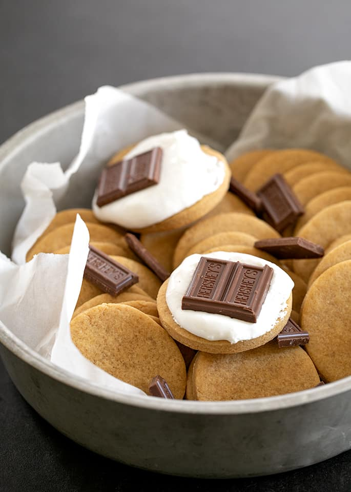 Round tin with graham cracker cookies with marshmallow fluff and chocolate