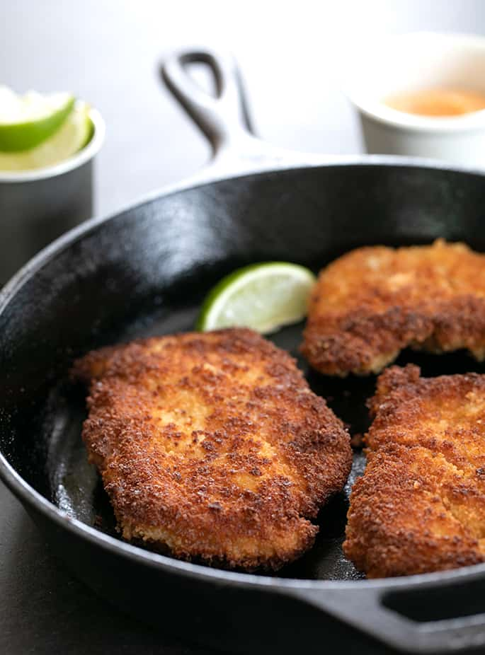 Spicy Chicken Cutlets in cast iron skillet with limes and dipping sauce