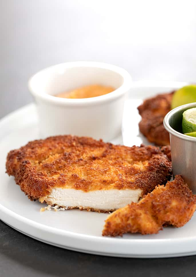 Spicy chicken cutlet on a plate with limes and dipping sauce