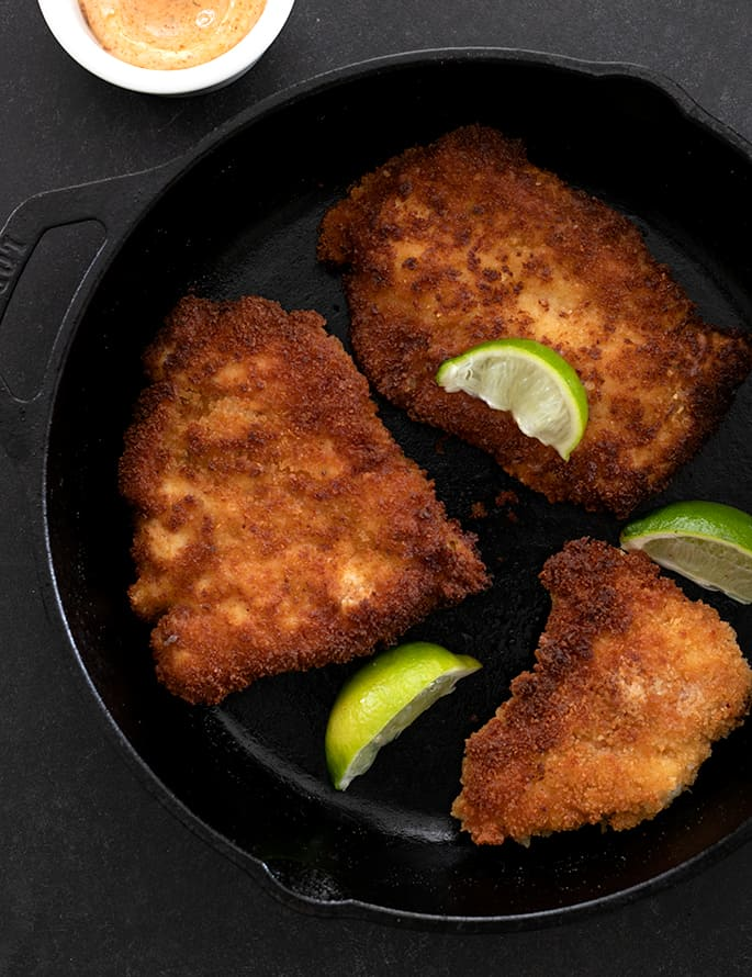 Spicy chicken cutlets in pan with limes overhead image