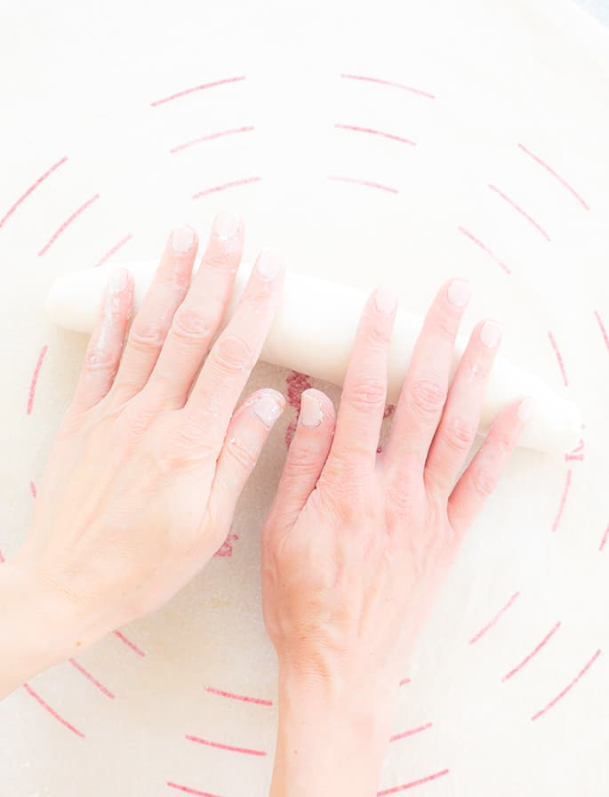 Two hands shaping a loaf of french bread dough