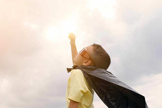 A young boy wearing sunglasses, a white shirt, and a cape raises his fist in the air, gazing into the sky.