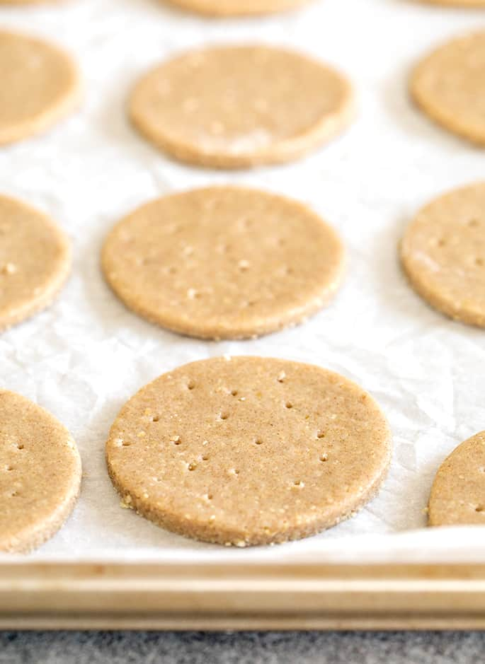 Raw shaped digestive biscuits on white paper on a tray