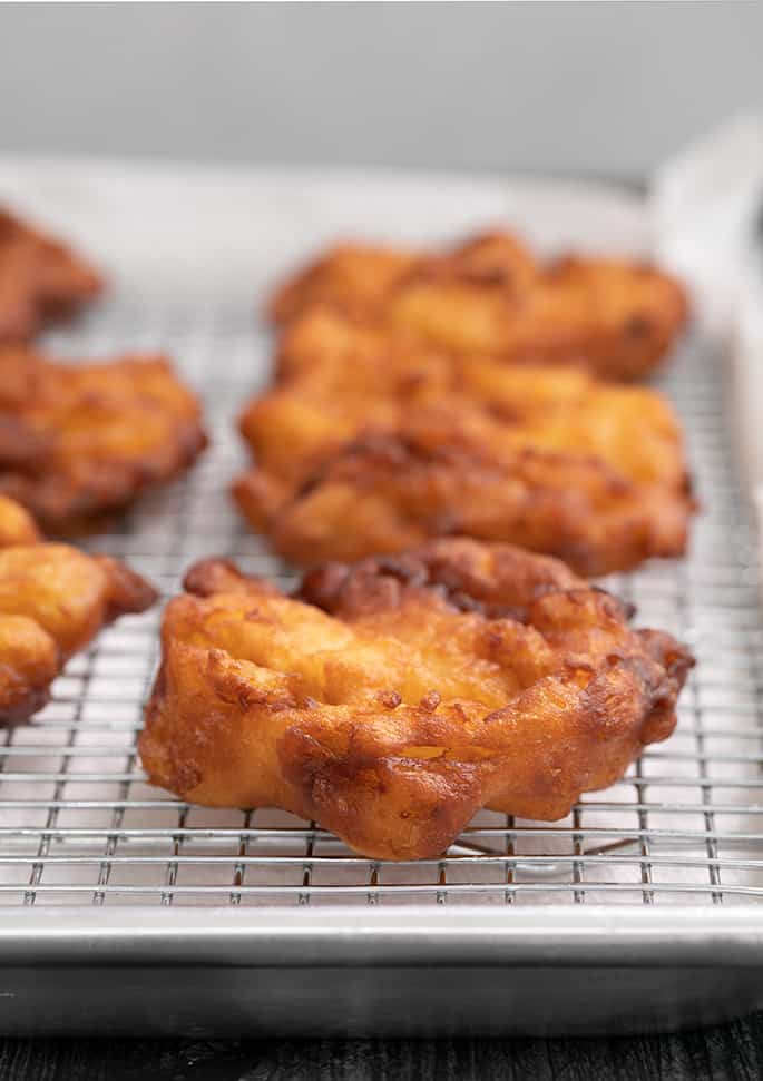 Apple fritters cooling on a wire rack