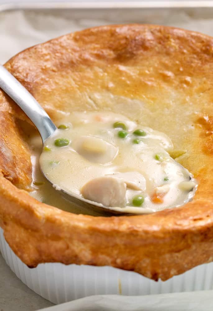 Chicken pot pie in casserole dish with serving spoon