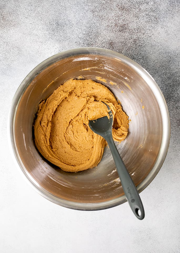 Gingersnaps cookie dough in a bowl with a black mixing spoon