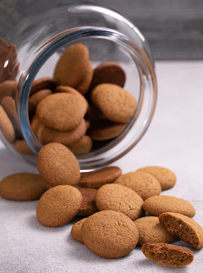 Gingersnaps poured out of glass jar onto white table