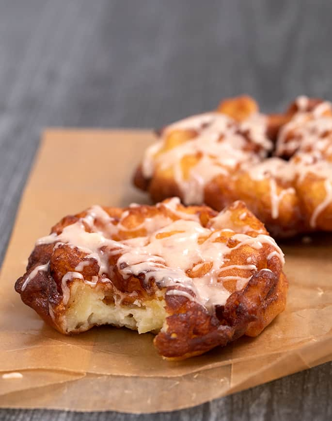 Two apple fritters with glaze on waxed paper one with a bite taken