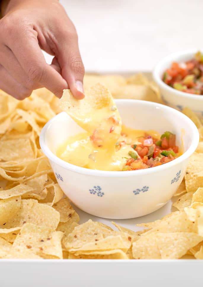 Hand dipping a chip in cheese sauce in a small white bowl with salsa on top