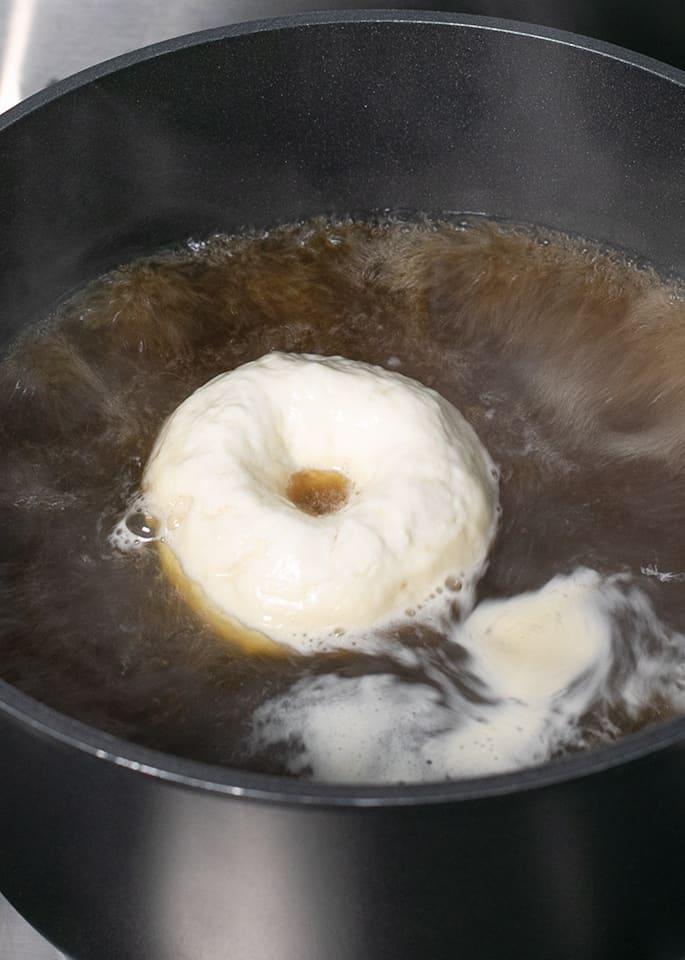 Raw bagel boiling in water in black pot