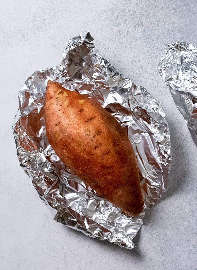 Raw sweet potato in foil partially unwrapped