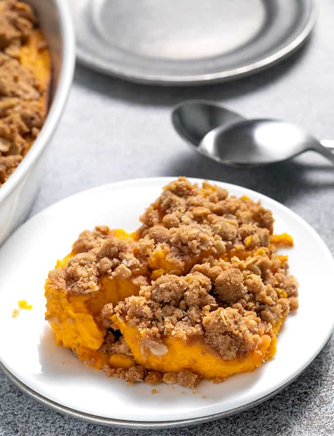 Sweet potato casserole serving on small white plate with spoons and serving dish