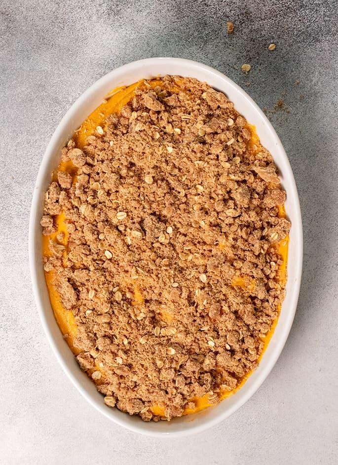 Sweet potato casserole unbaked in white baking dish overhead image