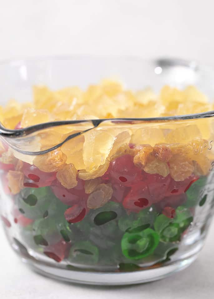 large glass measuring cup filled with yellow, green, and red candied fruit