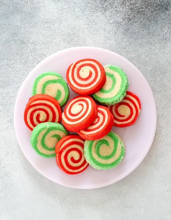 Overhead image of green and red striped pinwheel cookies on a plate