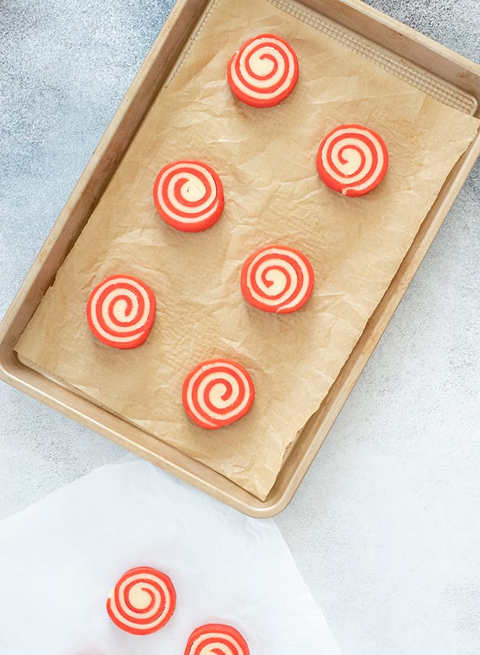 Overhead image of raw red and white pinwheel cookies on white paper and on lined baking tray