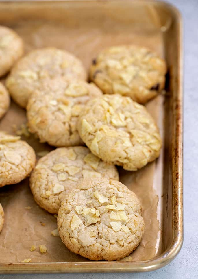 Potato chip cookies piled on baking tray lined with brown paper