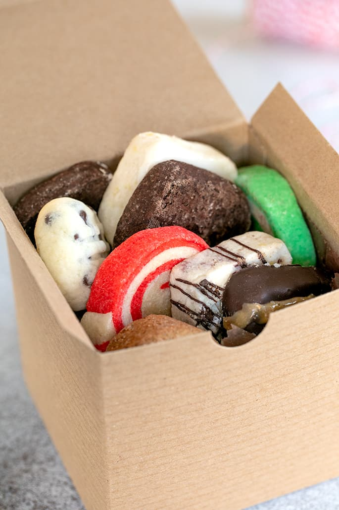 Small brown kraft box filled with assorted Christmas cookies